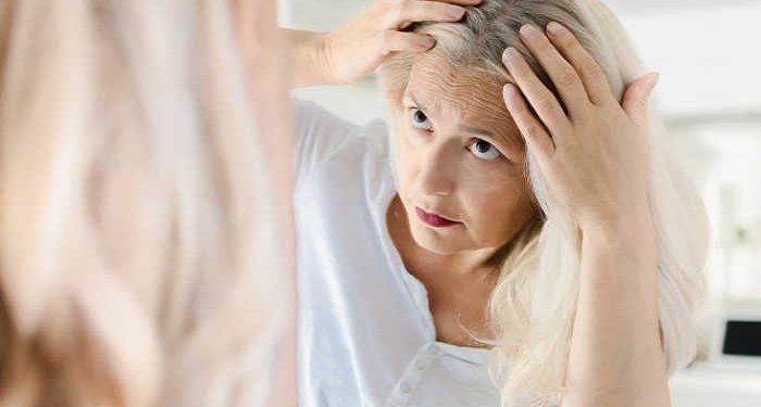 donna allo specchio cerca capelli bianchi