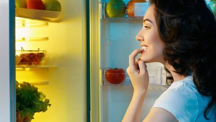 ragazza guarda in frigo